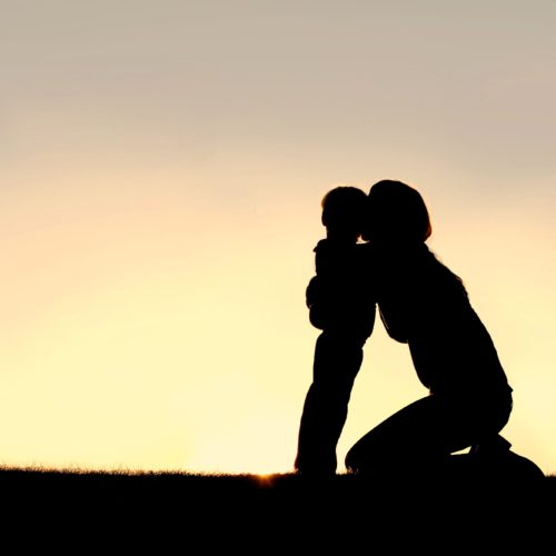 A silhouette of a young mother sitting outside, lovingly hugging her 2 year old toddler sun at sunset, with copy-space in sky.