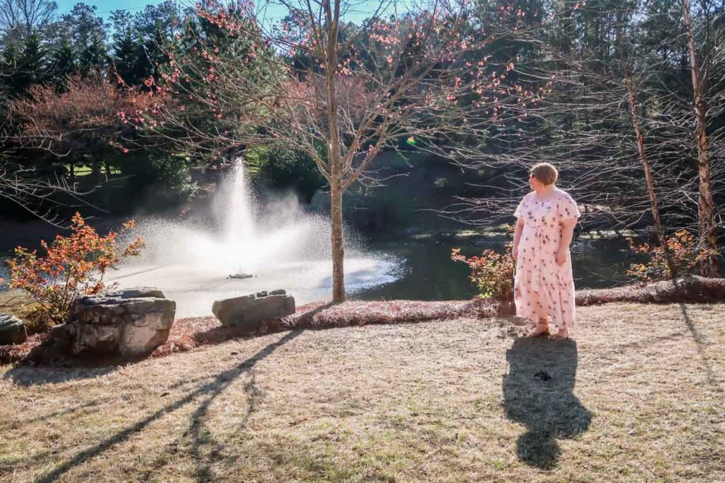 Lane Bryant Off The Shoulder Ruffled Maxi Dress in front of a pond with a fountain
